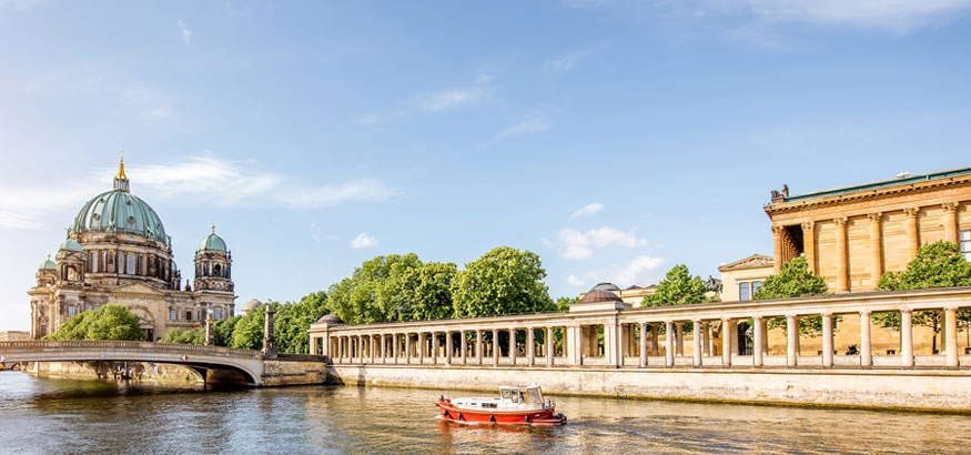 Tourist ship passing Museum Island and Berlin Cathedral on River Spree in Berlin, Germany.