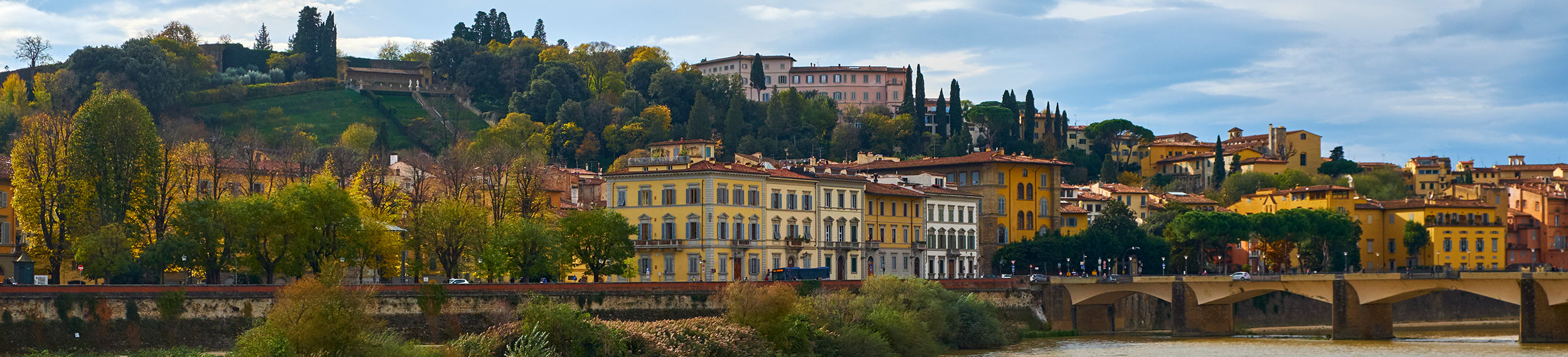 Colorful stucco villas, palazzo, stores and hotels overlooking the Arno River in Florence, Italy.