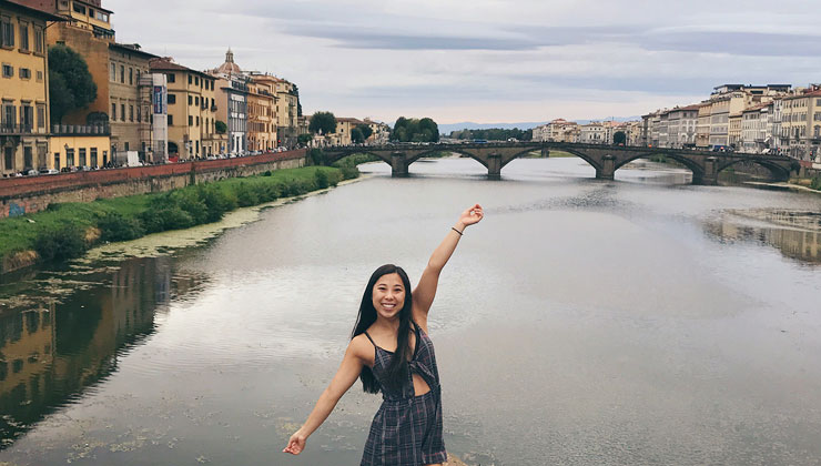 UC Davis student strikes a pose in front of a waterway in Florence, Italy.