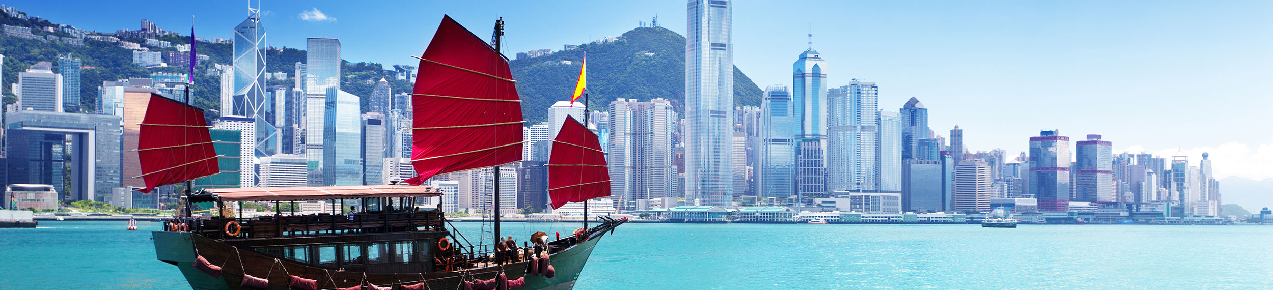A traditional Chinese junk ship with square red sails glides through the turquoise water with a buildings and blue sky in the background.