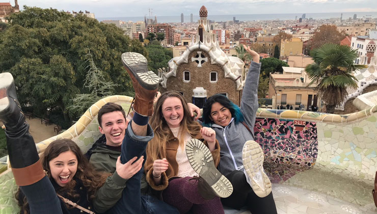 Four friends kick their feet up in the air and laugh at Park Güell in Barcelona, Spain.