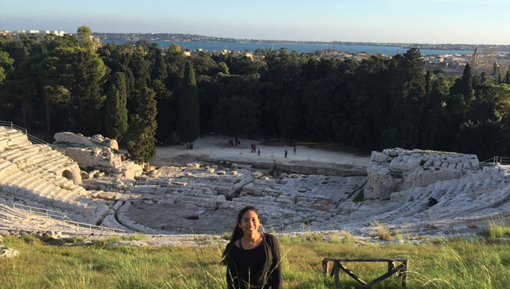 UC Irvine student poses in the grass above the empty Greek Theatre of Syracuse in Italy.
