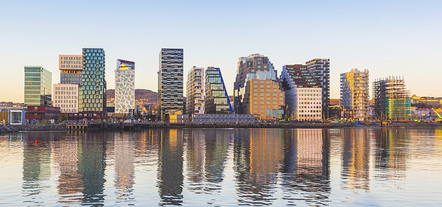 View of modern Oslo buildings, reflecting off the water at sunrise.