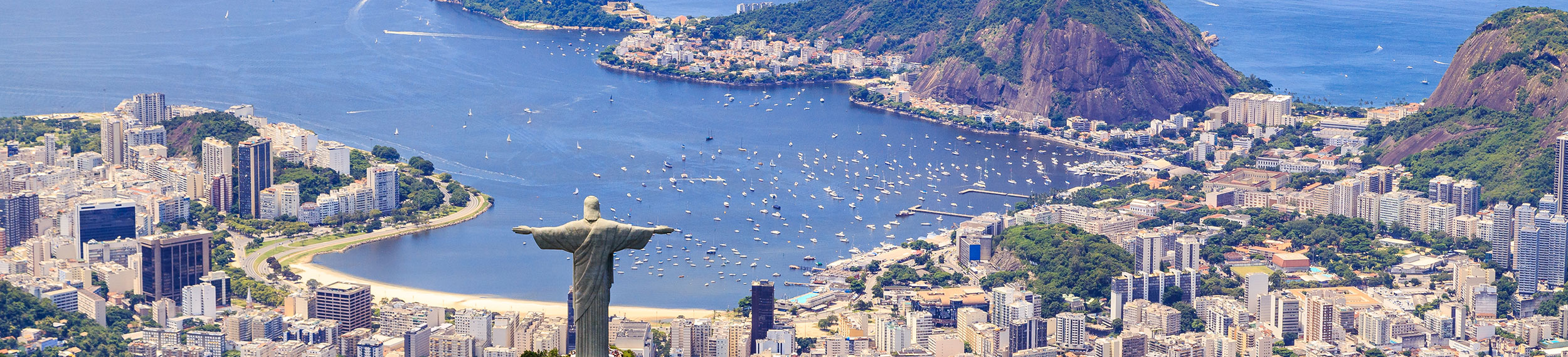 Aerial view of Christ The Redeemer Monument on Corcovado Mountain overlooking the water on a sunny day in Rio de Janeiro, Brazil.
