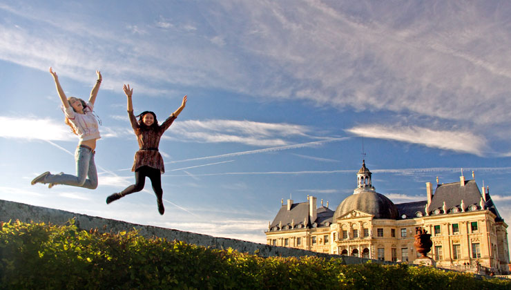 Students jumping at the Palace of Versailles in Versailles, France.