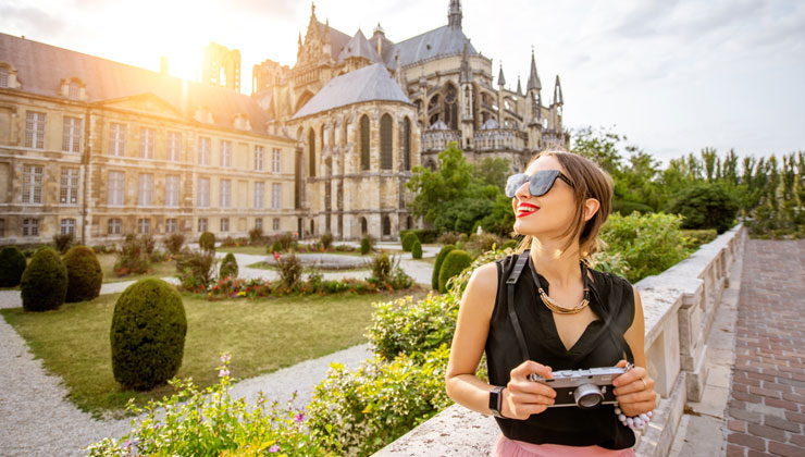 A female student holding a camera and looking to the side in front of Cathédrale Notre-Dame de Reims in Reims, France.