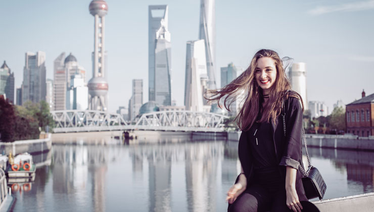 Female student in the foreground with the river and downtown skyline in the background in Shanghai, China.