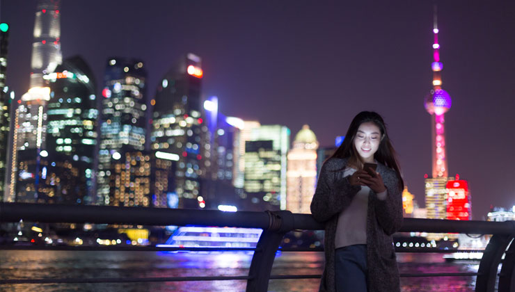 Student on her phone at night with the Oriental Pearl TV tower and downtown buildings in the background.