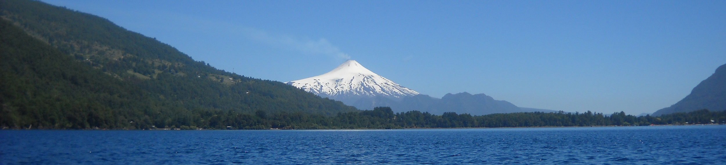 The snow covered Volcán Villarrica behind a big blue lake in Villarrica, Chile.