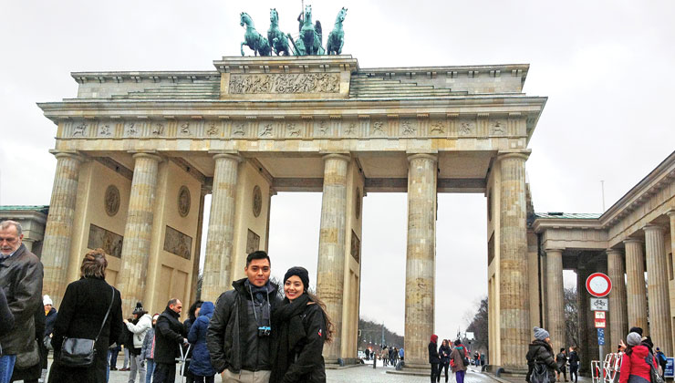 Two students smiling for the camera in front of the Brandenburg Gate in Berlin, Germany.
