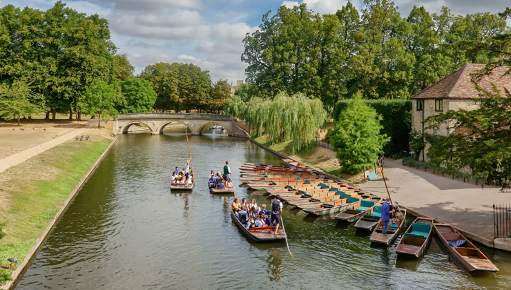 Punts on river Cam in Cambridge, England with a view of Trinity Bridge.