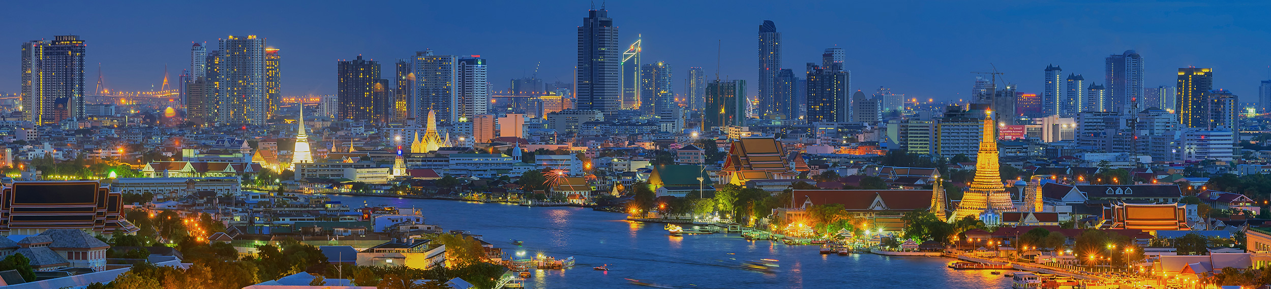 The Chao Phraya River Wat Arun curves around high-rise buildings at dusk in Bangkok, Thailand..