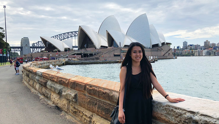 Student poses by the water with the Sydney Opera House in the background in Sydney, Australia.