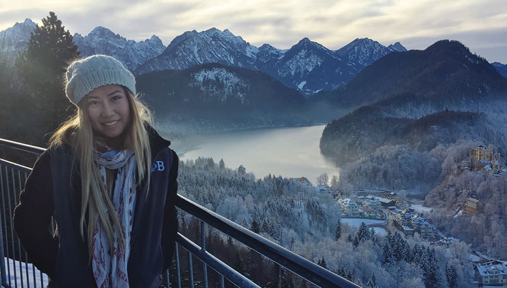 UC Santa Barbara student smiling for a camera with a view of Neuschwanstein Castle a lake and mountains covered in snow in Bavaria, Germany.