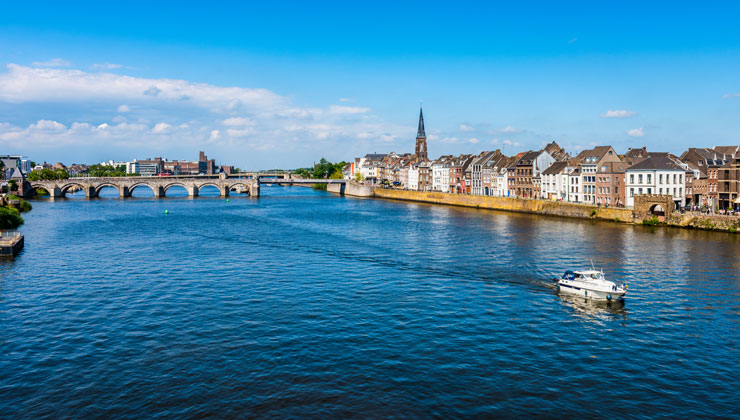 View of Maas River on a sunny day with a boat and Saint Servatius Bridge in the background in Maastricht, Netherlands.