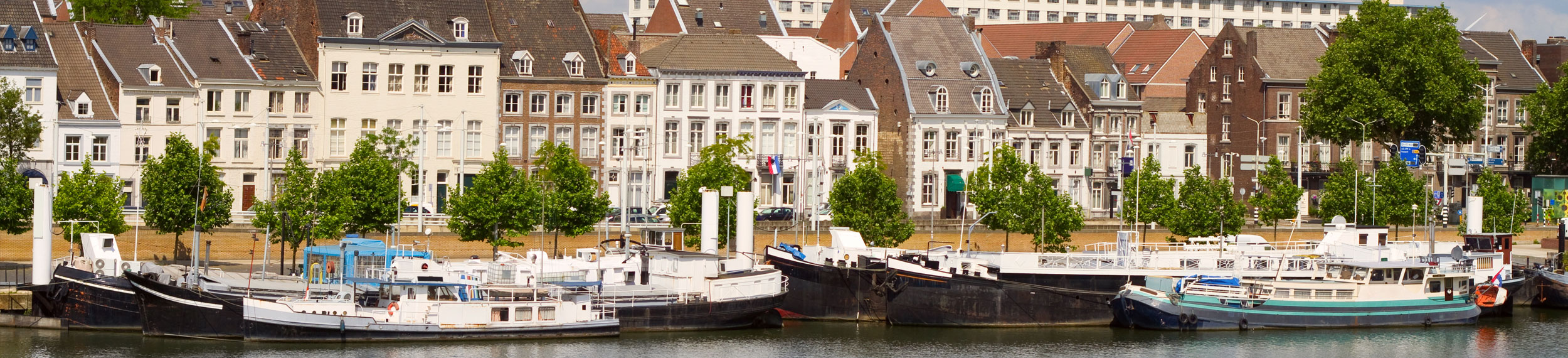 Landscape shot of buildings and boats along the Meuse River in Maastricht, Netherlands.