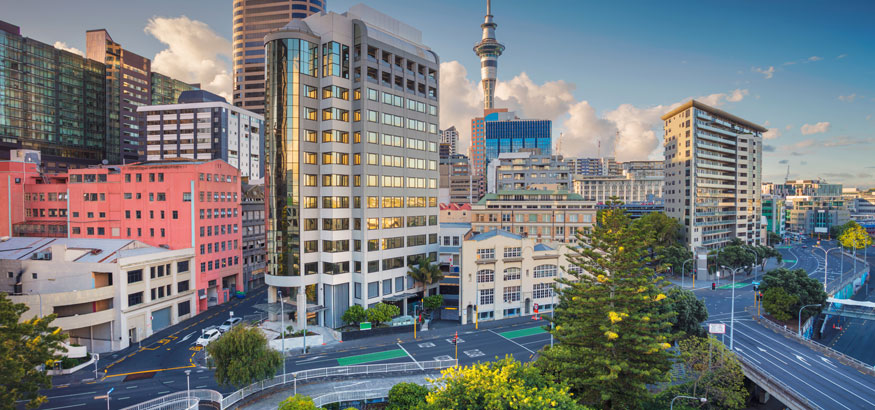 Aerial cityscape image of downtown buildings and Sky Tower in Auckland, New Zealand.