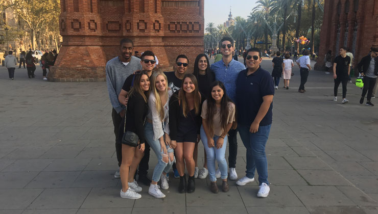 A group of ten students smiling at the camera with the view of the arch of the Arco de Triunfo de Barcelona in Barcelona, Spain.