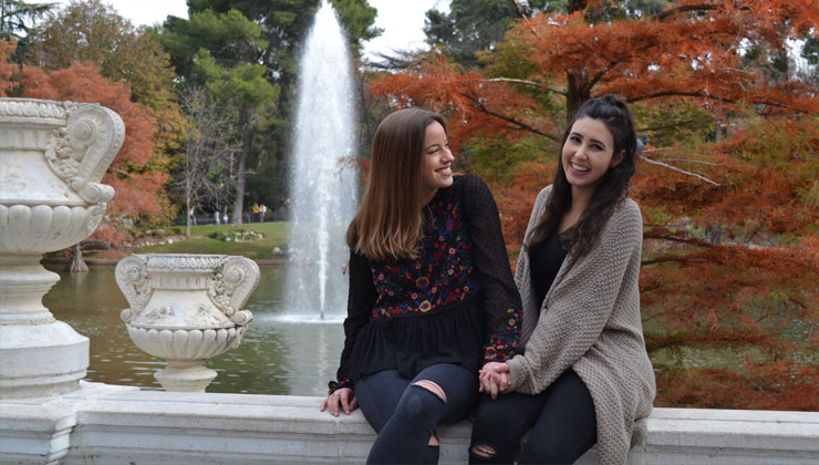 Two smiling students sitting at a fountains in Barcelona, Spain.