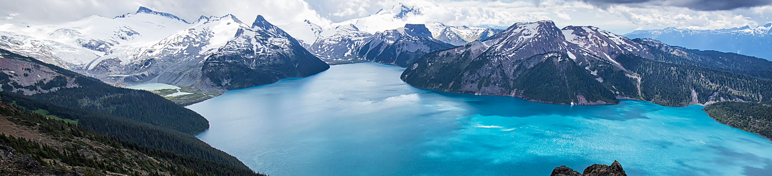 Garibaldi Lake surrounded by snow-capped mountains viewed from Panorama Ridge in summer in British Columbia, Canada.