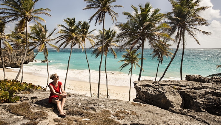 Student sits on rocks near palm trees and Bottom Bay Beach in Barbados.