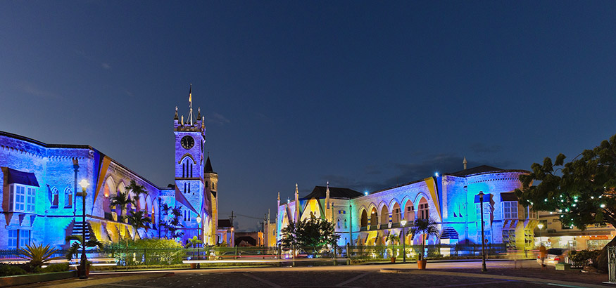 Yellow, blue, pink, and green colors lighting up the Parliament Building at night in Bridgetown, Barbados.