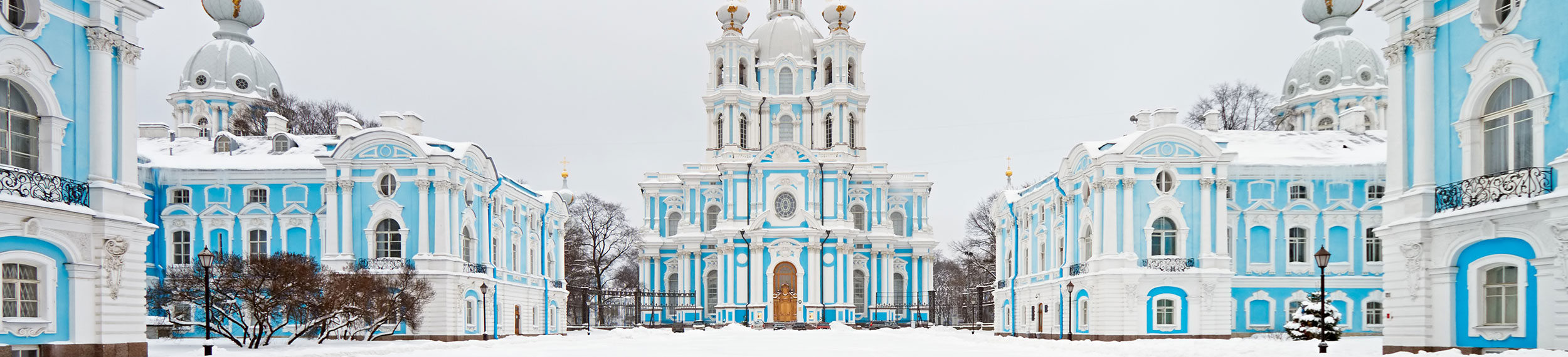 The light blue and white cathedral and surrounding buildings of Smolny Cathedral covered in snow in St. Petersburg, Russia.