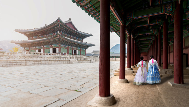 Students in Hanbok traditional dress explore Gyeongbokgung Palace in Seoul, Korea.