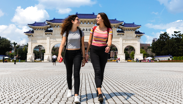 Two friends looking at each other and smiling with a view of the DaXiao Gate in Taipei Taiwan.