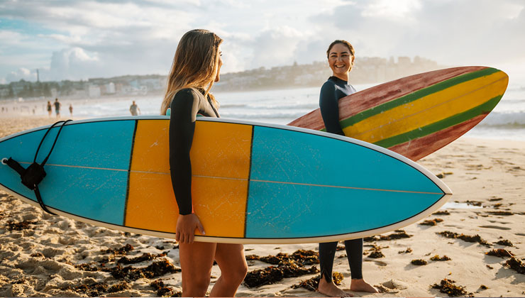 Two female friends with surfboards in Melbourne, Australia.